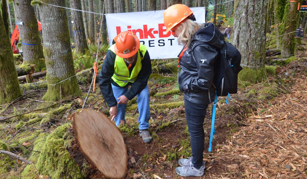 Mike Cloughesy and Erin Isselmann examine a stump at the Pacific Logging Congress